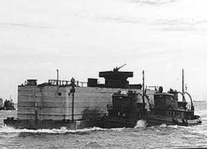 Concrete caisson Phoenix being towed by tugs